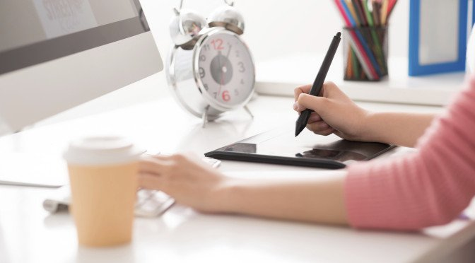 Cropped image of a graphic designer using digital tablet in his work on the foreground